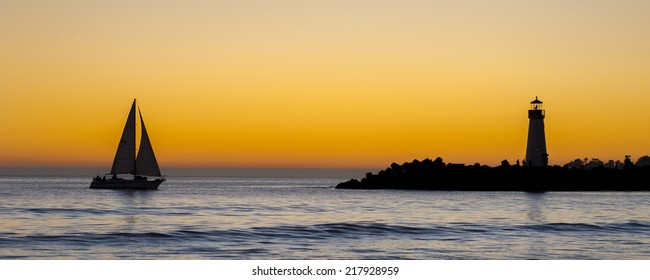 Lighthouse and surf boat at sunset