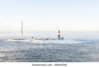 Lighthouse and telecommunication antenna on an isle in a vaporizing sea at winter