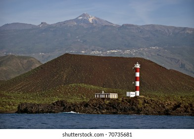 A lighthouse in Tenerife (Faro de Rasca), Canary Islands. In the background - Volcano El Teide. El Teide, a volcano on Tenerife is the highest mountain of Spain 12,188.3 feet (3,715 m).