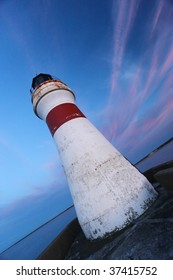 Lighthouse in a tilted position with colorful evening sky