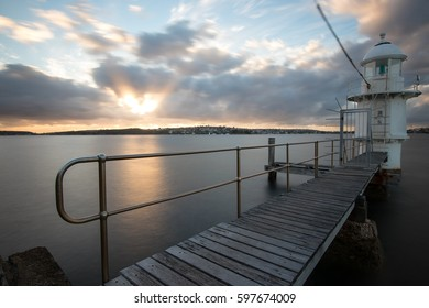 Lighthouse and timber jetty at sunrise with reflection in the water at Bradleys Head Sydney Australia