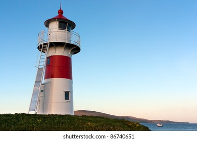 Lighthouse of Torshavn, Faroe Islands, with low evening sun .  On the background Nolsoy island .