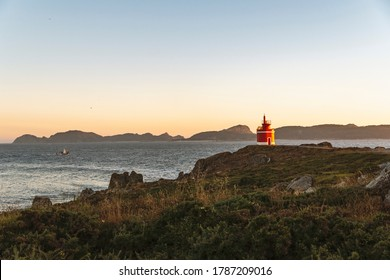 Lighthouse, or tower, red on a cape on the steep Atlantic coast of northern Spain. At the bottom of the image, sea and islands. With a beautiful evening light