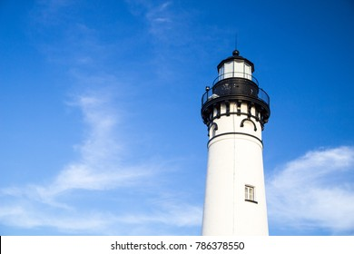 Lighthouse Tower Under Blue Sky With Copy Space. The tower of the Au Sable Lighthouse shot under a sunny blue sky in horizontal orientation with copy space, Pictured Rocks National Lakeshore.