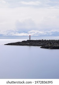 Lighthouse view. A lonely lighthouse at the end of a stony breakwater immersed in a silky smooth sea with white clouds at the horizon. A symphony of blues