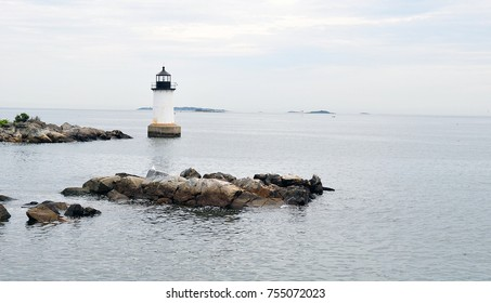 Lighthouse in the water on rocky ocean sea shore