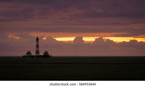 Lighthouse Westerheversand at sunset, North Sea in Germany