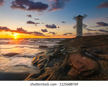 Lighthouse windmill, sunset over the sea Baltic Sea, Swinoujscie, Poland