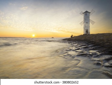 Lighthouse windmill, sunset over the sea Baltic Sea, Swinoujscie, Poland
