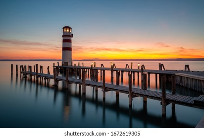 Lighthouse with wooden footbridges paths on lake during sunset