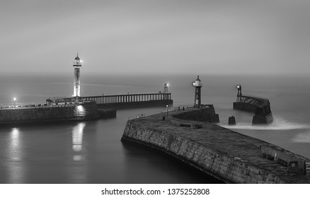 Lighthouses on the East and West Piers. Whitby Harbor.  North Yorkshire. North Sea. England. UK. Long exposure. Black and white photography. Main focus on piers