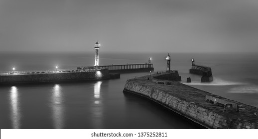 Lighthouses on the East and West Piers. Whitby.  Scarborough. North Yorkshire. North Sea. England. UK. Long exposure. Black and white photography. Main focus on piers
