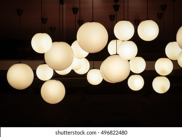 Lighting ball hanging from the ceiling on the black background