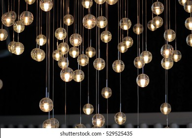 lighting balls on the chandelier in the lamplight,  light bulbs hanging from the ceiling, lamps on the dark background, selective focus, horizontal