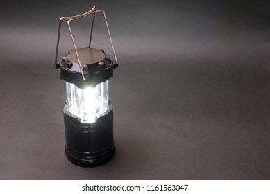 Lighting black LED lantern in front of dark background