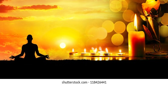 Lighting candles at bokeh background and man doing meditation at sunset. Space for your text