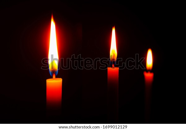 The lighting candles, Burning candle on black background, Candle in hand, Candle in the dark, Design for the background. The light of the yellow stick candle in the dark at night.