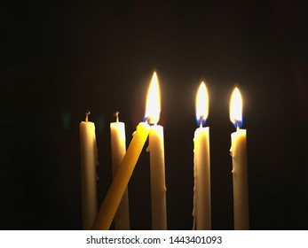 Lighting up candles in a dark room, as a symbol for light up your life concept, far from burnout syndrome, close up