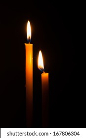 Lighting candles on a black background.