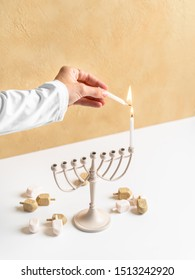 Lighting candles on a menorah for the Jewish holiday of Chanukah. Celebrating the Hebrew holiday Hanukkah with dreidels as a hip young adult in a neutral color palette.