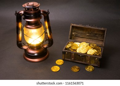 Lighting copper color LED lantern and treasure chest with gold coins in front of dark background