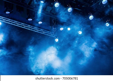 Lighting equipment on the stage of the theatre during the performance. The light rays from the spotlight through the smoke. Blue rays of light.