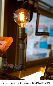The lighting in front of the cash register, retro industrial style, is a bright tungsten light bulb,