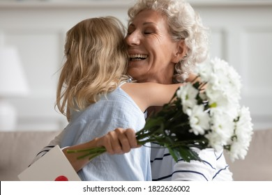 Lighting from happiness. Laughing mature grandmother or elderly foster mom folding to breast small kid girl grandchild or adopted daughter receiving greeting card and flowers on Mothers Day or March 8