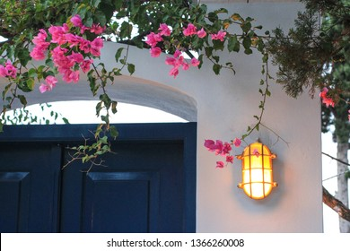 Lighting lantern on the white wall and blue door, typical entrance to greek house, Spetses town, Spetses island, Greece