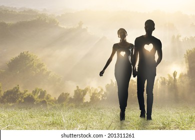 Lighting love, Silhouette of Asian couple hold hands walking on grassland.