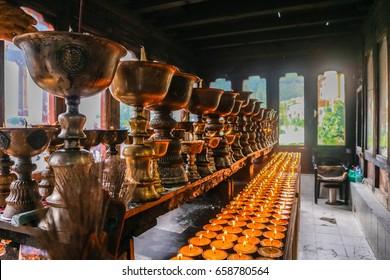 Lighting of praying candles, brushed metal pots in Zangdhopelri Monastery in Thimphu, Bhutan, South Asia