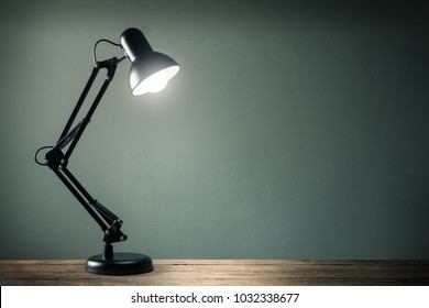 lighting retro desk lamp on old wood table with space of rough cement wall in vintage color tone
