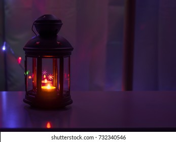 lighting from small candle in black lantern in the night from christmas celebration event with soft focus small light background
