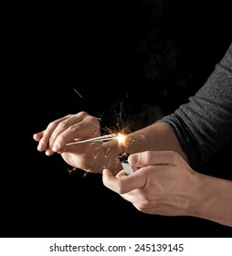 Lighting up a sparkler with lighter, low-key composition isolated over the black background