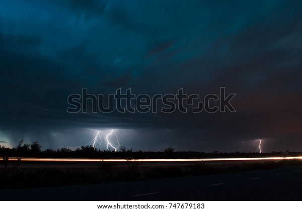 Lighting strikes in the distance with highway in the foreground