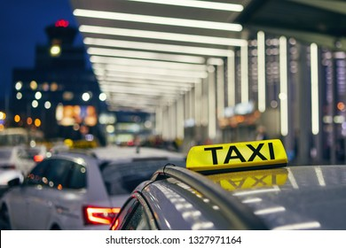 Lighting taxi sign on the roof of car against airport terminal at night.