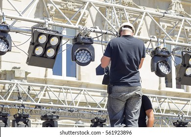 lighting technician iinstalling professional  lighting equipment for concert stage , installation with led lights and projectors