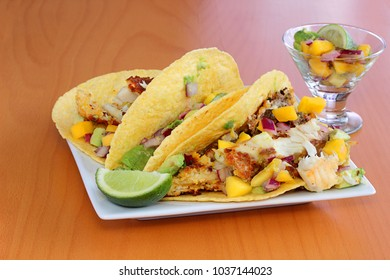 Lightly fried fish in a corn tortilla shell, served with mango chutney and a fresh slice of lime