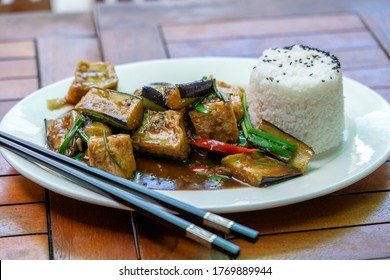 Lightly fried tofu and stew with eggplant, onion, garlic, gravy sauce on white plate, close up