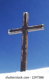 A lightly frost-touched wooden cross, high on a snowy Swiss mountain ridge with fine flakes of snow blowing past on a strong wind. Symbolises steadfastness and steadiness in the face of adversity.