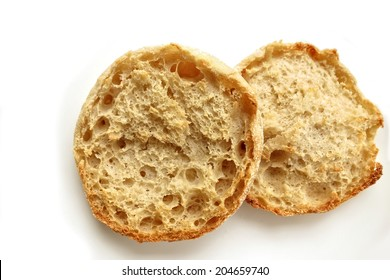 A lightly toasted English Muffin on white.