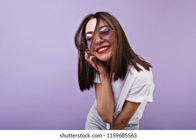 Lightly-tanned caucasian girl with sincere smile touching her face. Laughing brunette woman having fun during photoshoot on purple background.
