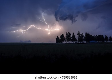 Lightning above field and cemetry with trees on the horizon. Lighning in cross shape and clouds in front.