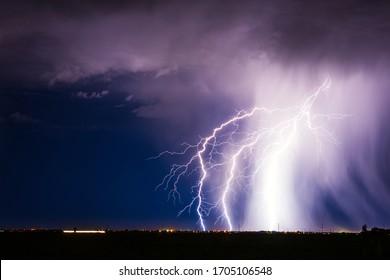 Lightning bolt strike from a thunderstorm over a city