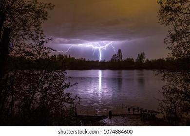 Lightning bolt as summer storm passes over carp fishing lake, Marlow, England, United Kingdon
