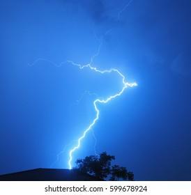 The lightning in the dark blue sky.