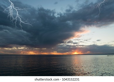 lightning falling on the sea at sunset during a thunderstorm
