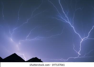 Lightning flashing across the night sky above some houses.