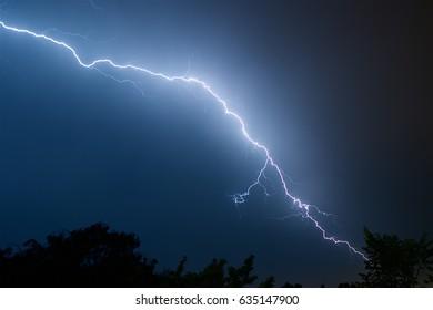 Lightning in the night dark blue sky. May thunderstorms.