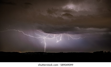 Lightning at night over Industrial Landscape in the Distance